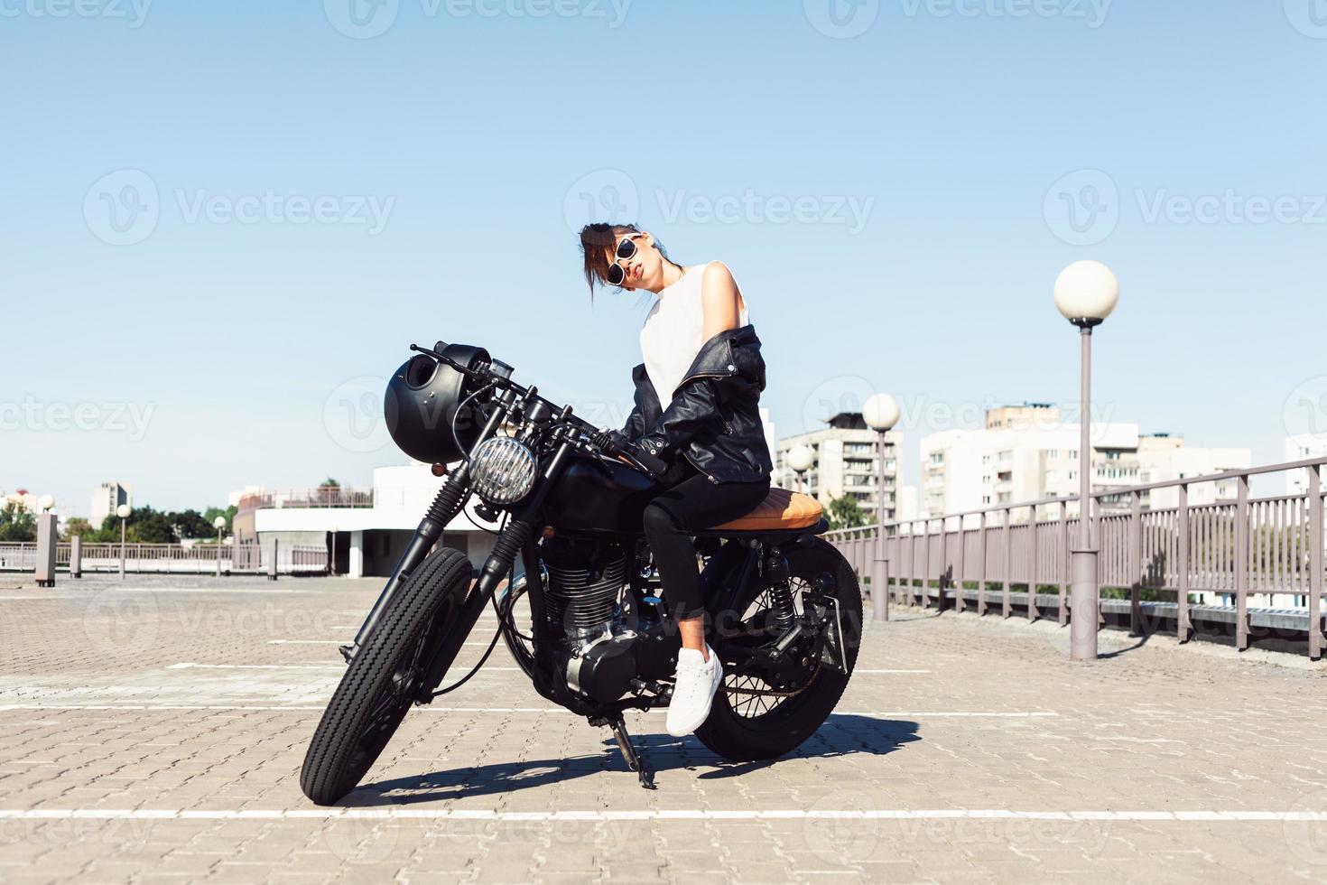 Biker girl sitting on vintage custom motorcycle photo