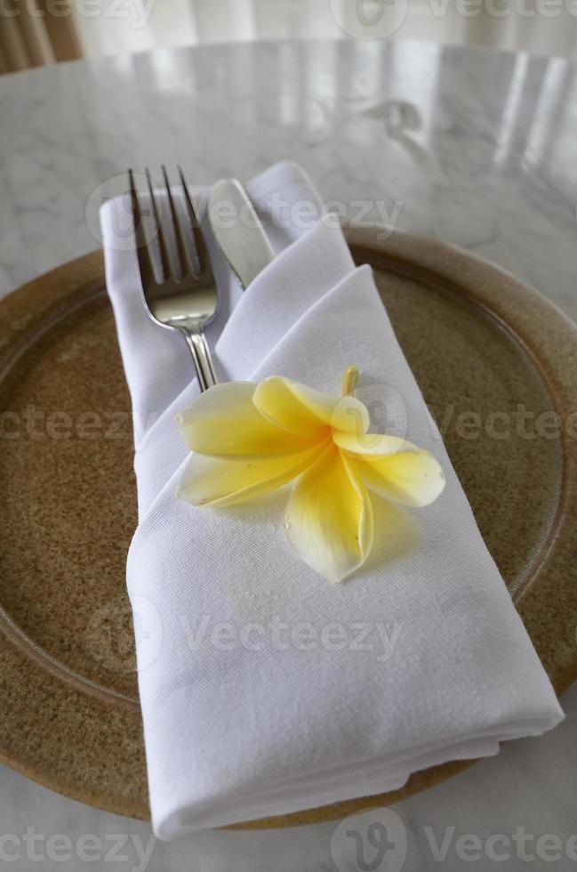 plato con servilleta de lino doblada cuchillo y tenedor, flor de loto foto