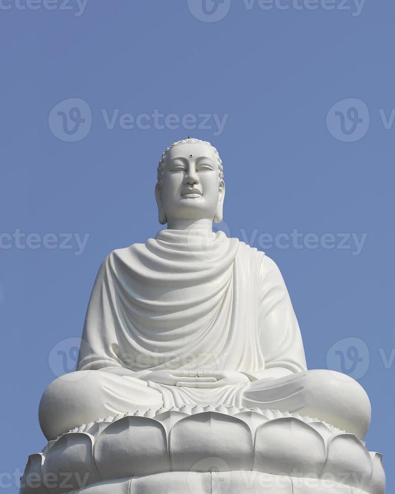 White Buddha statue sitting in lotus flower photo