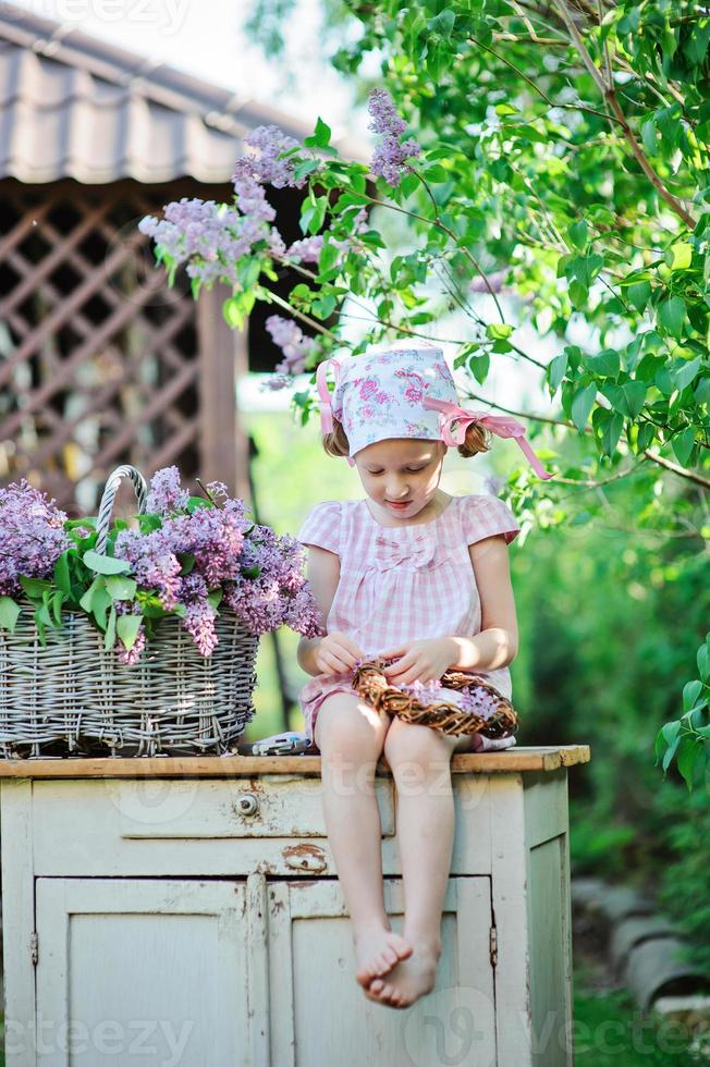 child girl making lilac wreath in spring sunny garden photo