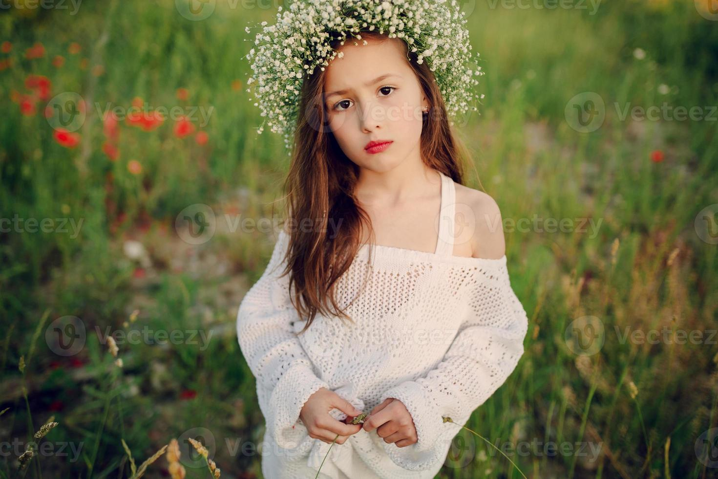 beautiful little girl posing in a skirt wreath of poppies photo