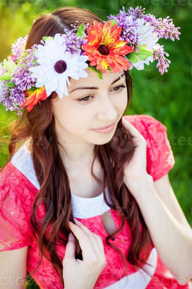 Beautiful young woman with wreath flowers  in the spring garden photo