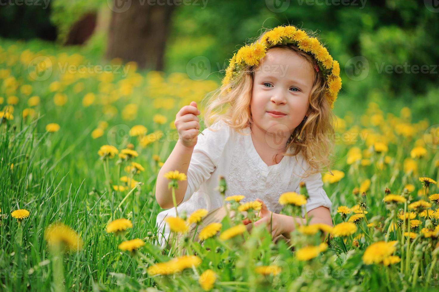 Linda niña rubia en corona de diente de león en campo de primavera foto