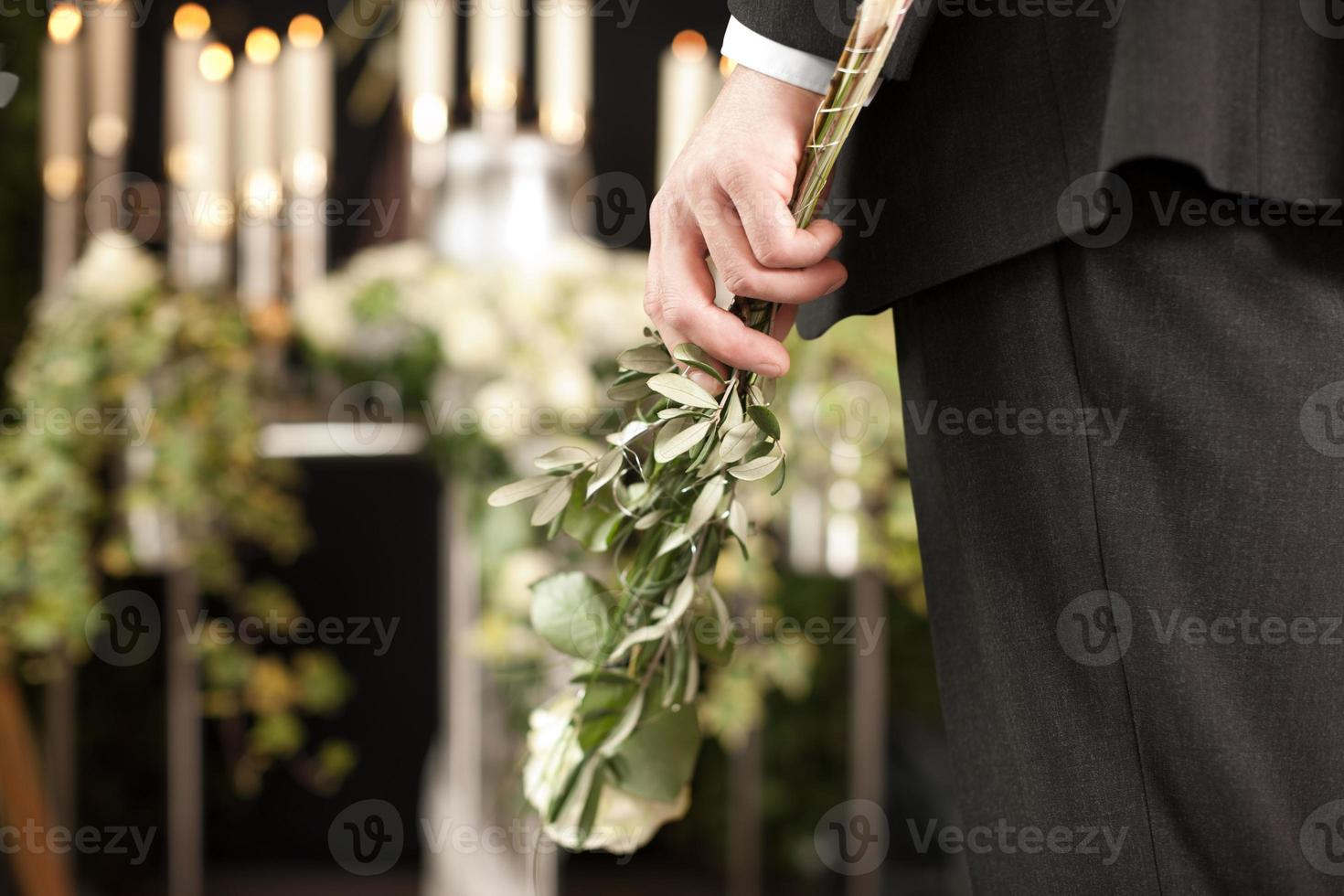 Grief - man with white roses at urn funeral photo