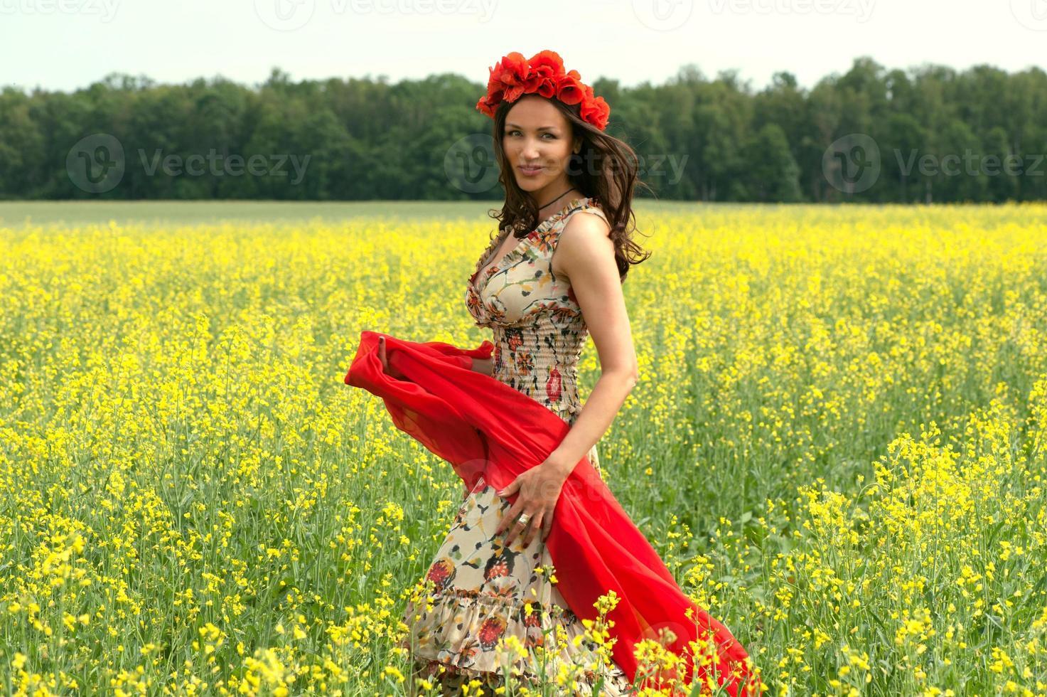 jovem morena usando coroa de flores no campo de verão foto