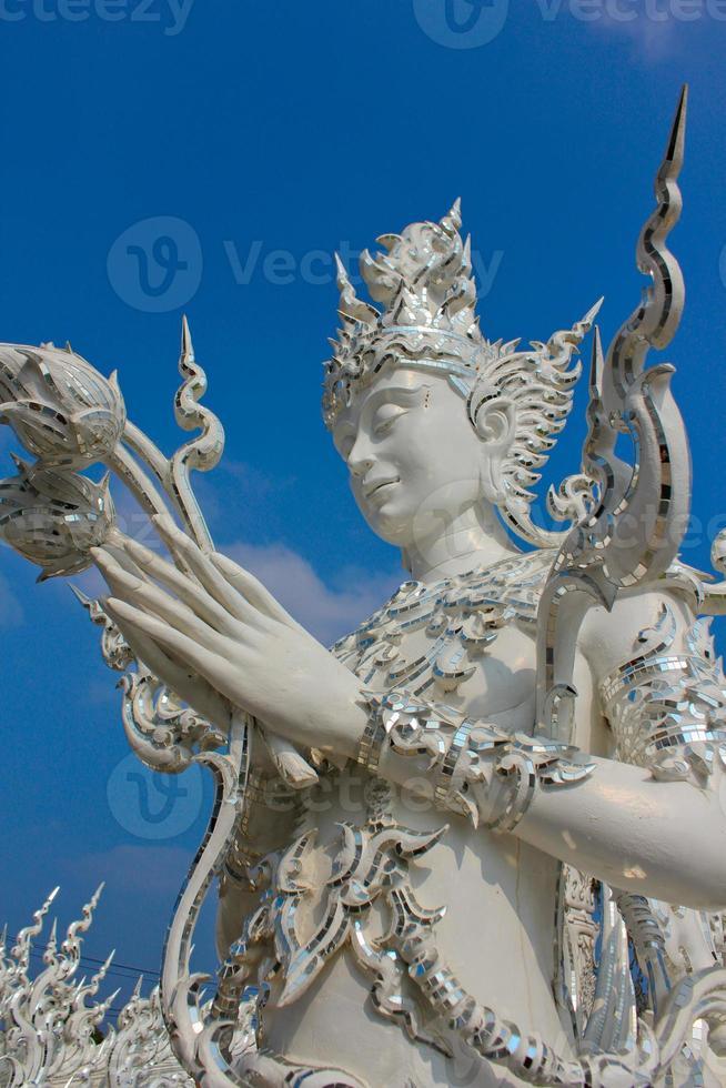 escultura blanca tailandesa con lotos en las manos foto