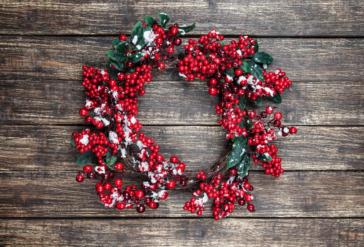 Holly christmas wreath on wooden table. photo