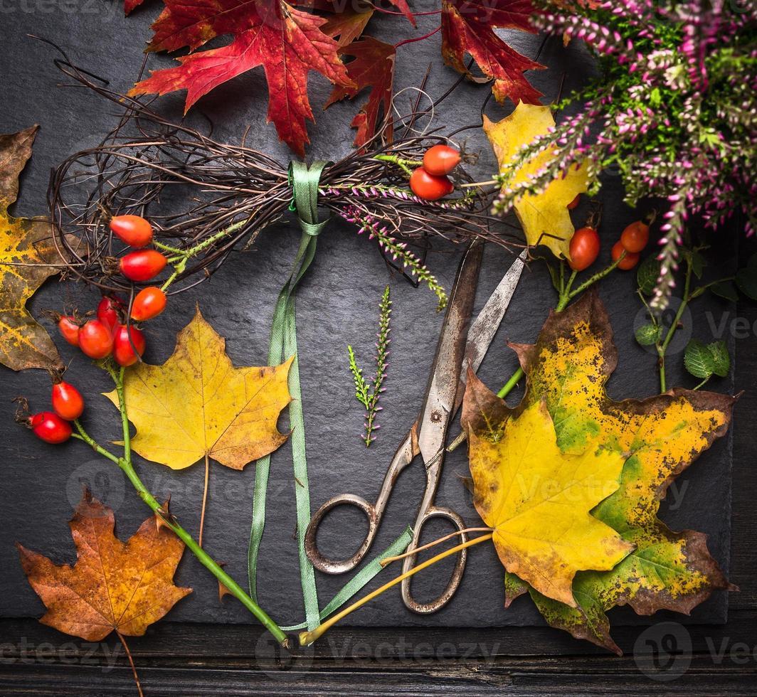 coroa de outono fazendo com folhas coloridas, galho e tesouras vintage foto