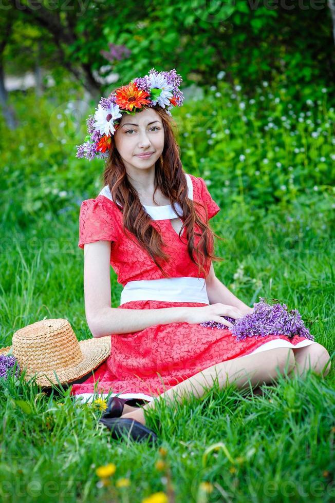 Bella mujer sentada en una ofrenda floral en un prado foto