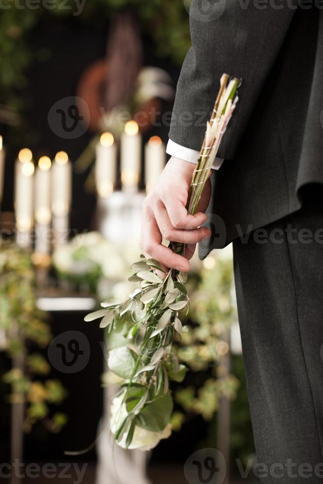 luto - homem com rosas brancas no funeral da urna foto