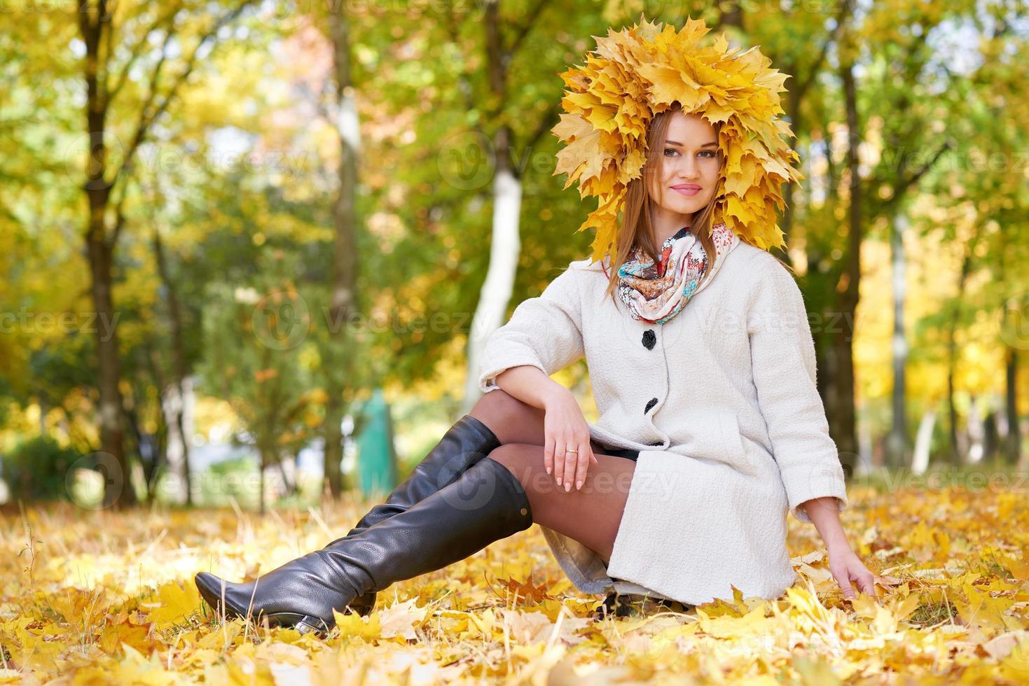 garota sentada nas folhas no outono parque da cidade foto