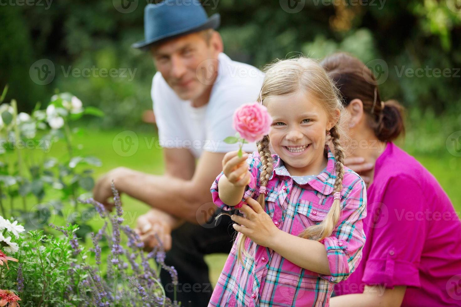 Girl in garden with granny and father showing flower photo
