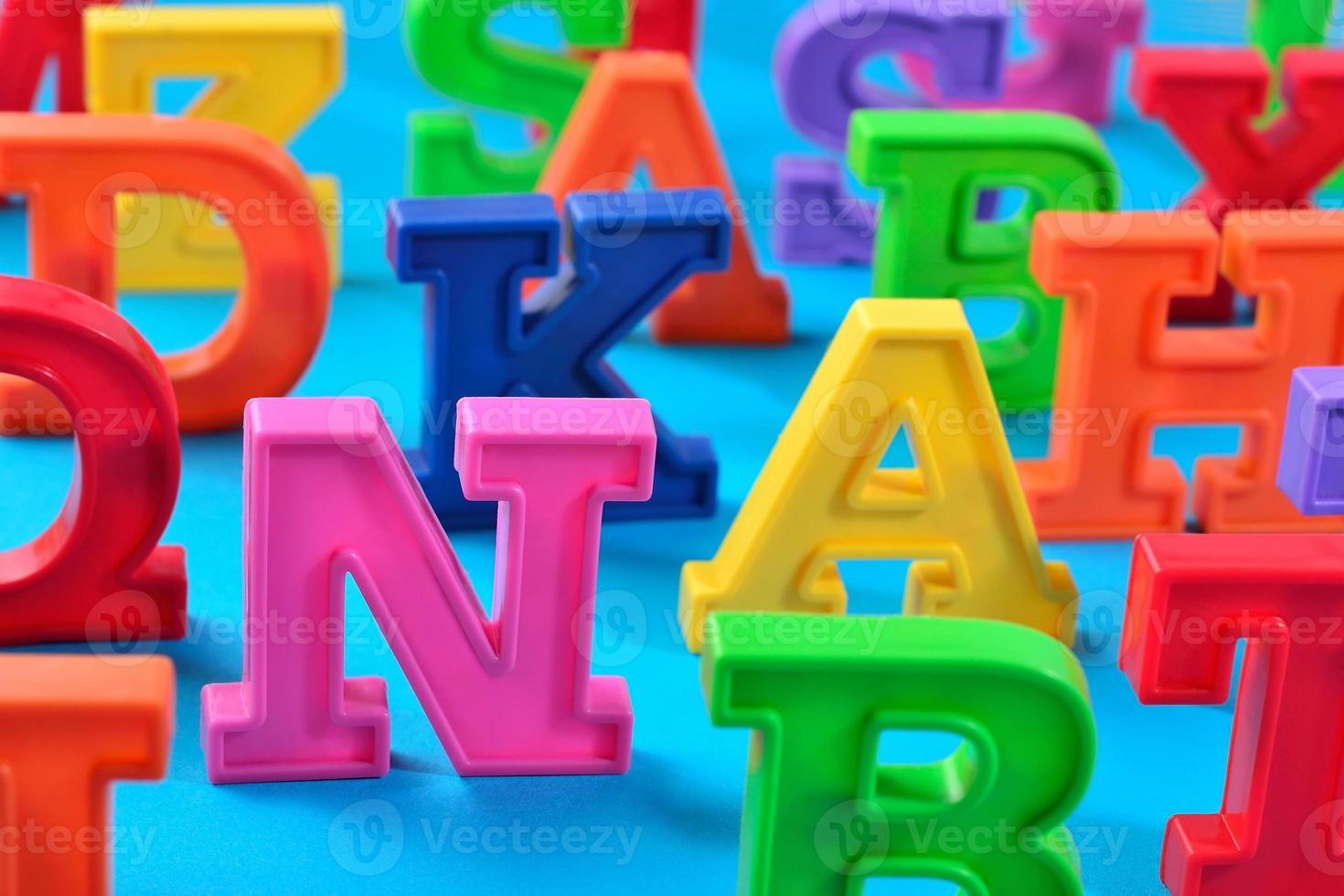 Letras del alfabeto de colores de plástico de cerca en un azul foto