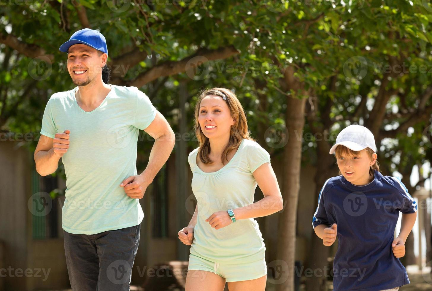 parents with son jogging outdoors photo