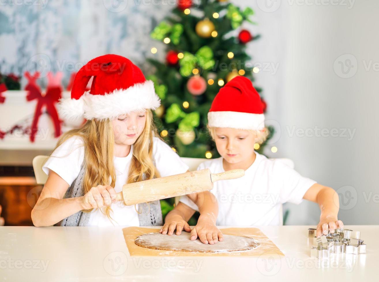 niños preparando galletas de navidad foto