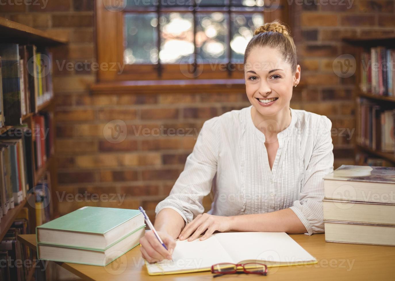 maestra rubia corrigiendo en la biblioteca foto