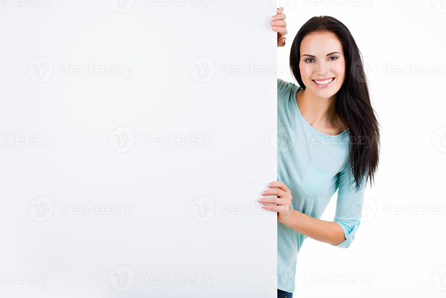 Happy smiling beautiful young woman showing blank signboard photo