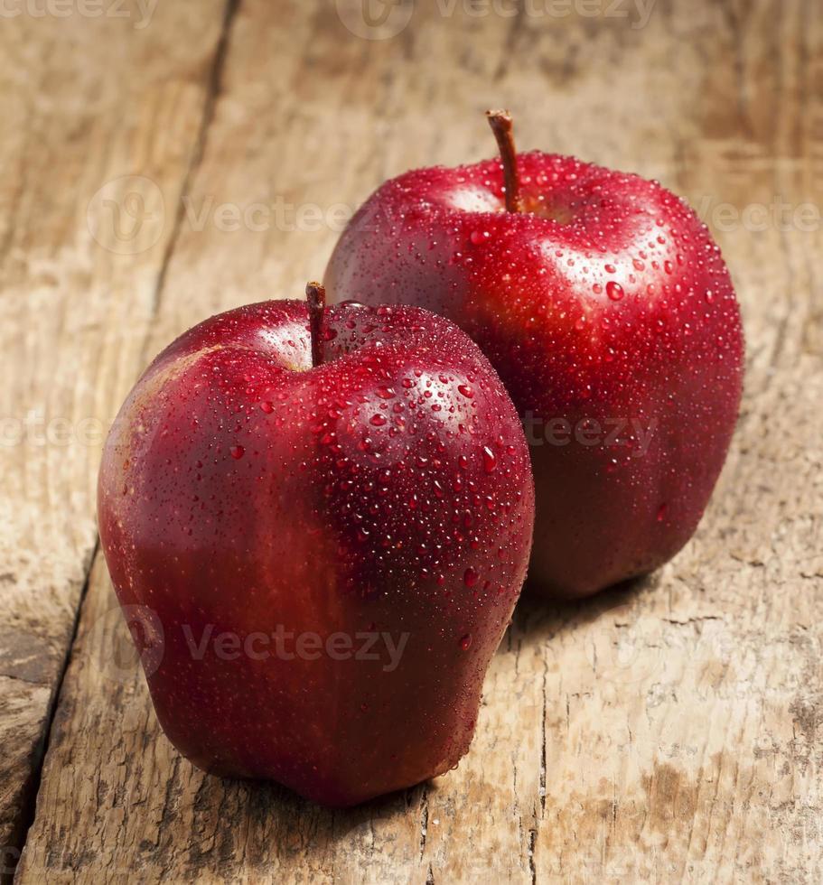Manzanas rojas con gotas de agua sobre una mesa de madera foto