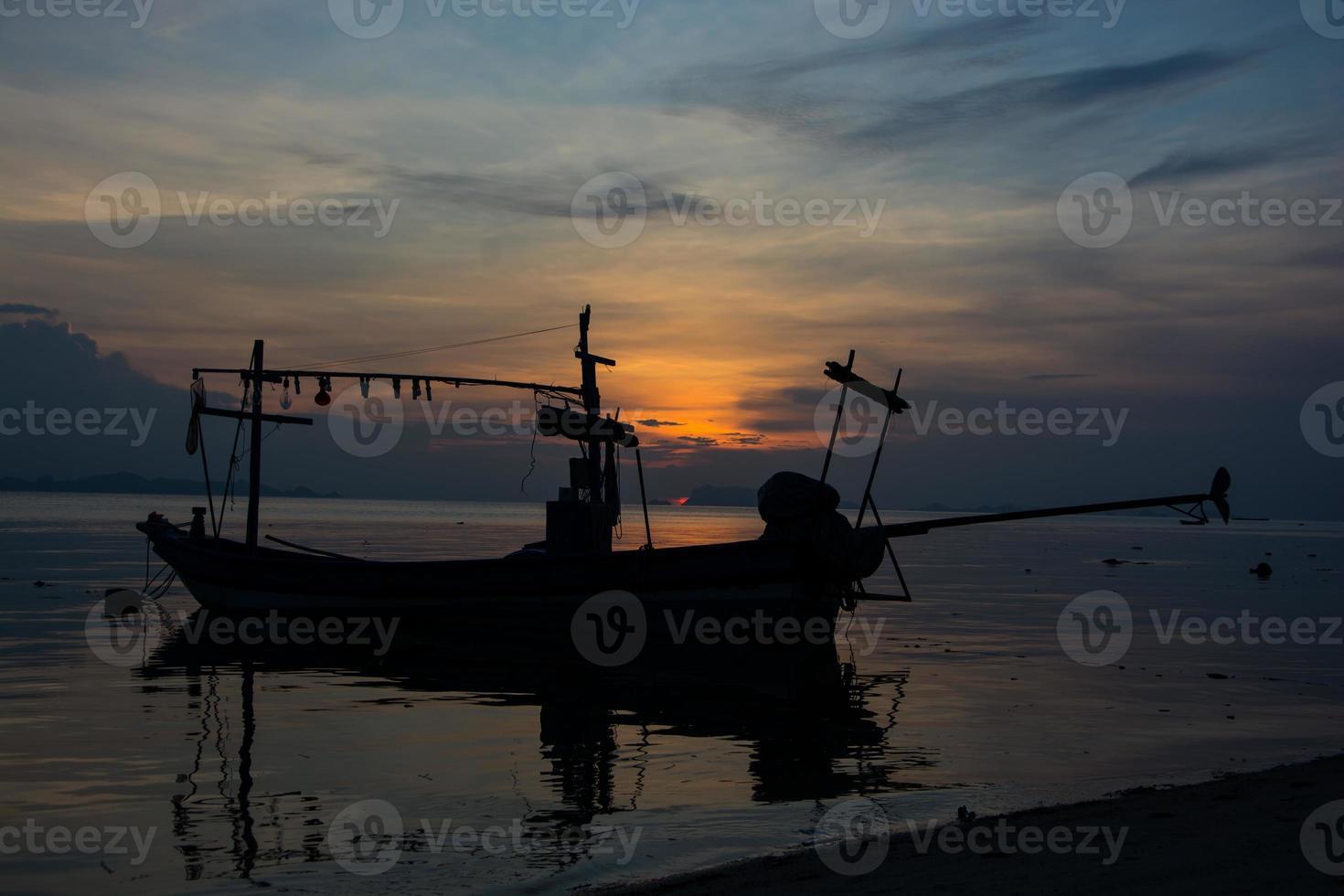 Bote de cola larga silueta con tragaluz de puesta de sol foto