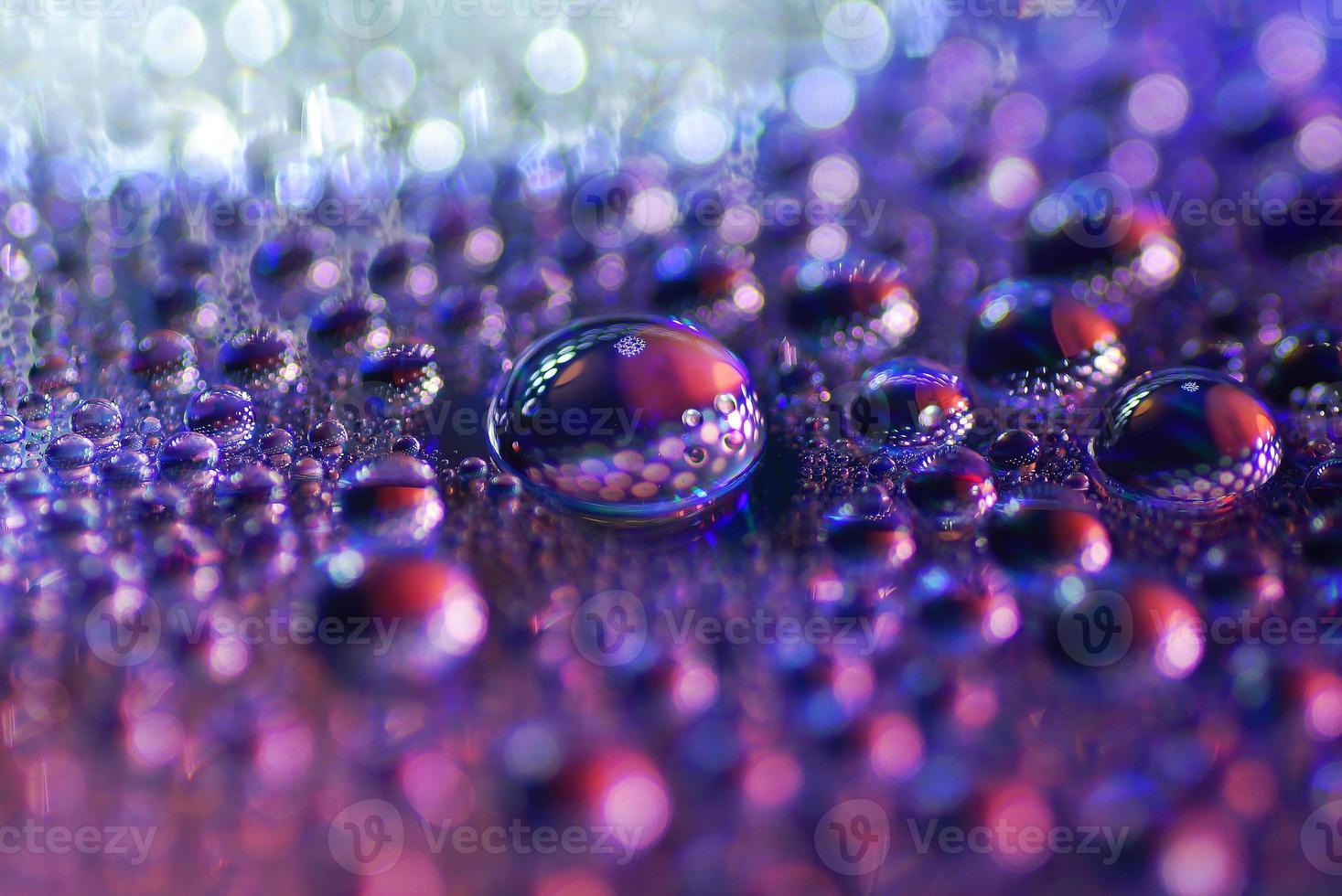 Macro de gotas de agua sobre una superficie de dvd, luz bokeh foto