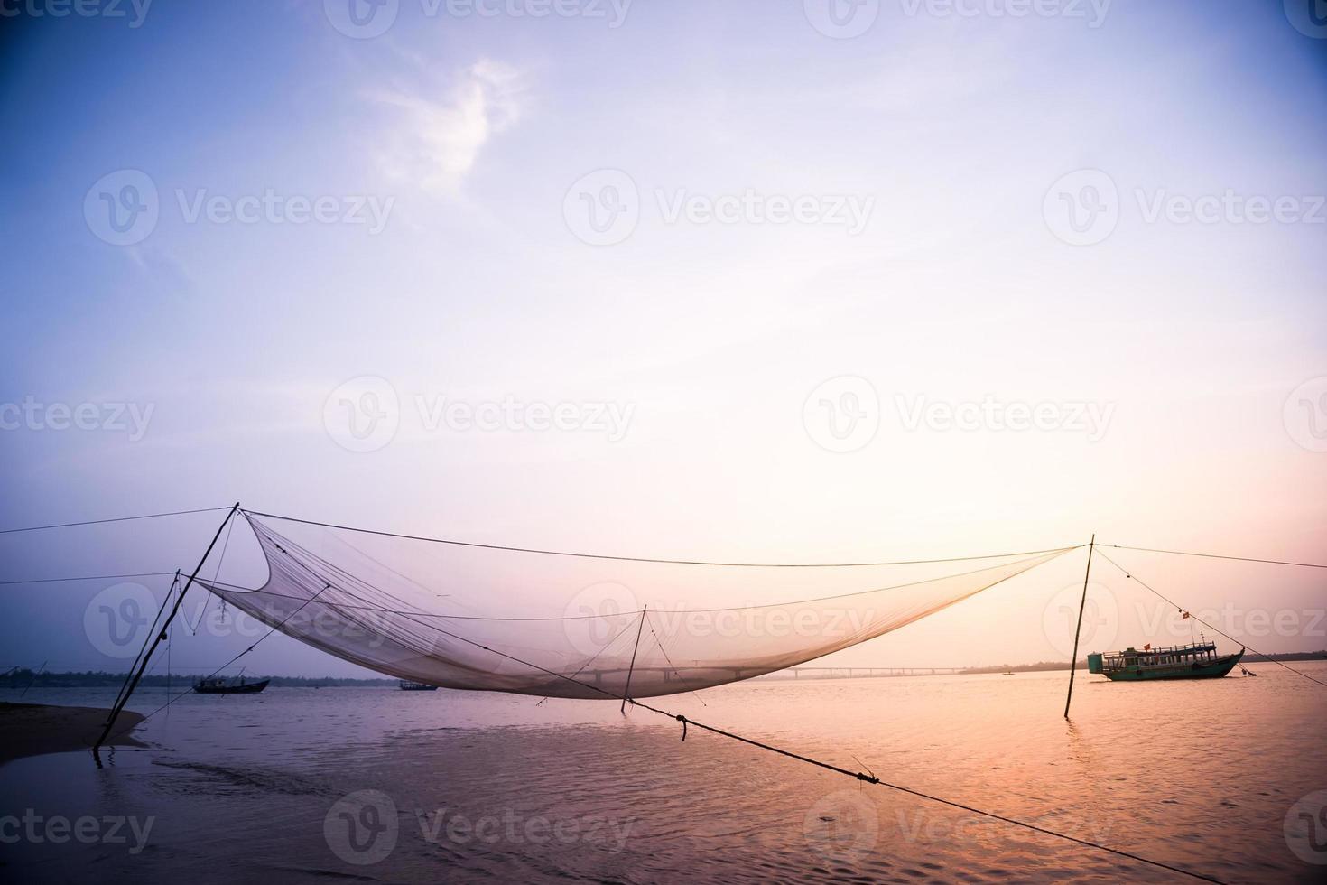 escena tranquila de la red de pesca contra el atardecer púrpura. foto