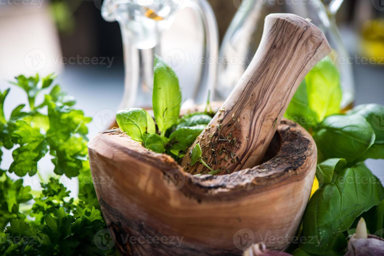 hierbas frescas y especias en mortero de madera foto