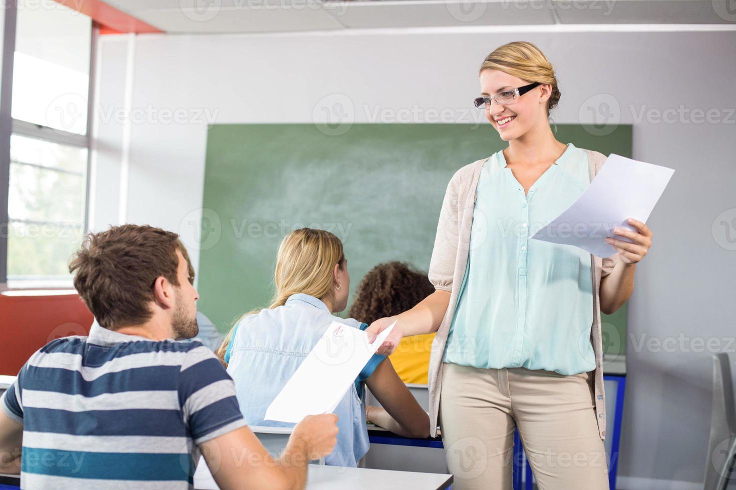 profesor entregando papel al alumno en clase foto