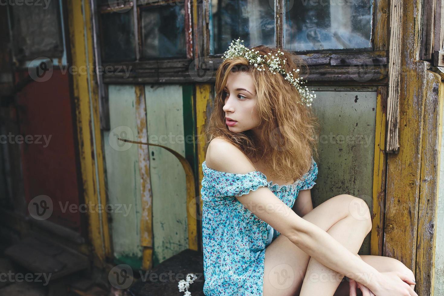 joven y hermosa niña sentada en la puerta foto