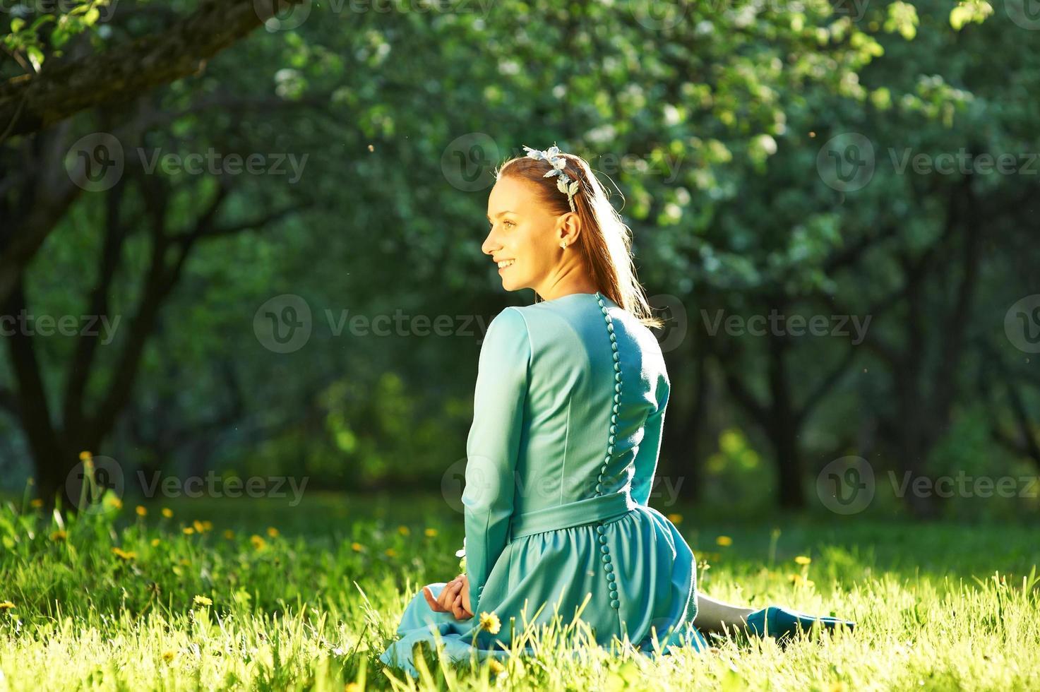 mujer en vestido entre flores de manzano foto