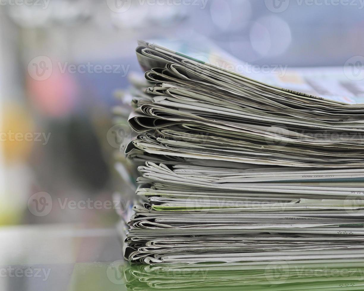 Stack of folded news papers on blurry background photo