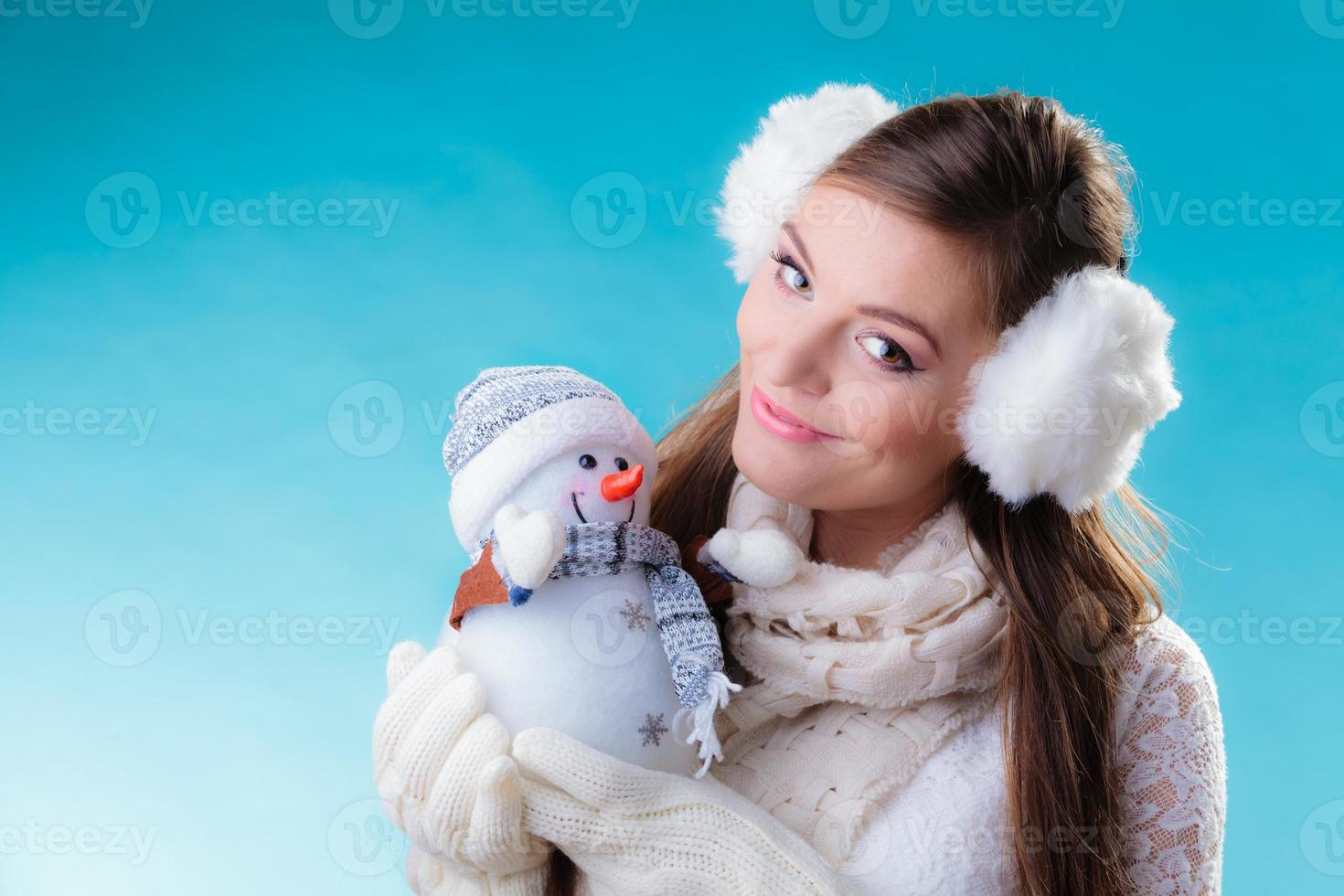 Woman in warm clothes holding snowman toy. photo
