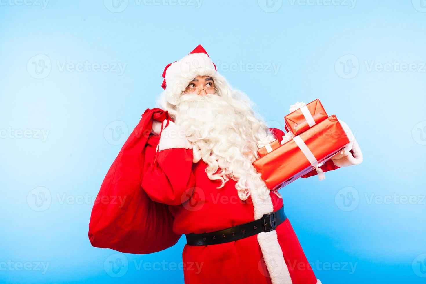santa claus with gifts on hands on blue background photo