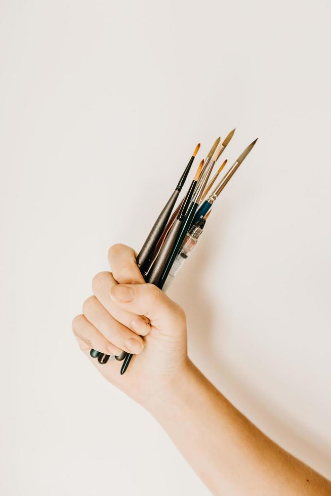 Cropped person carrying set of paintbrushes photo