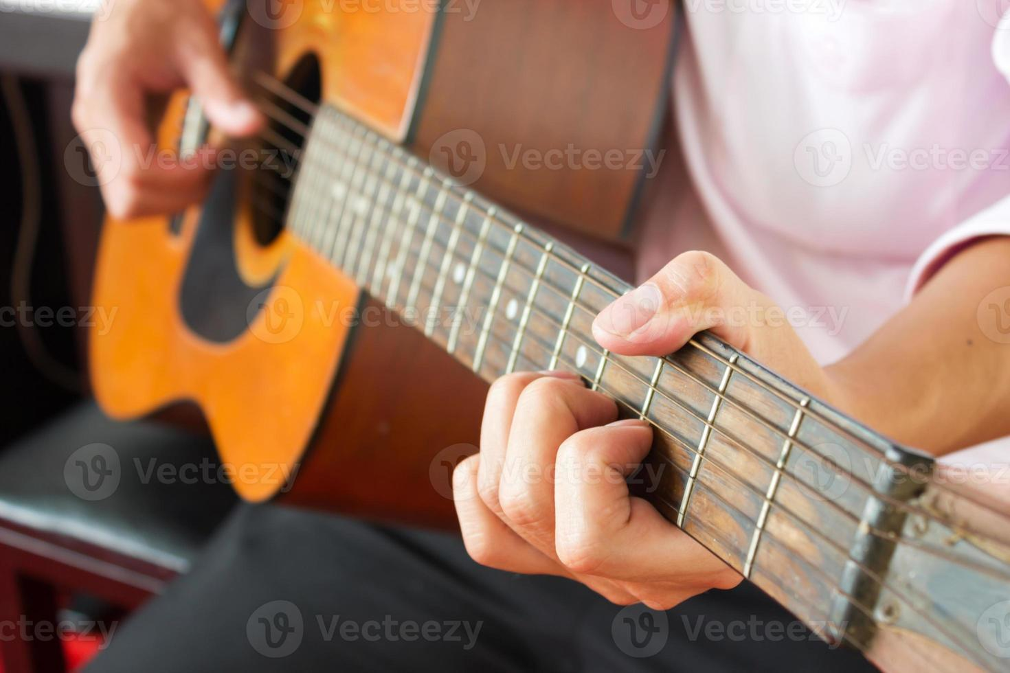 Closeup man's hands playing classic guitar. photo
