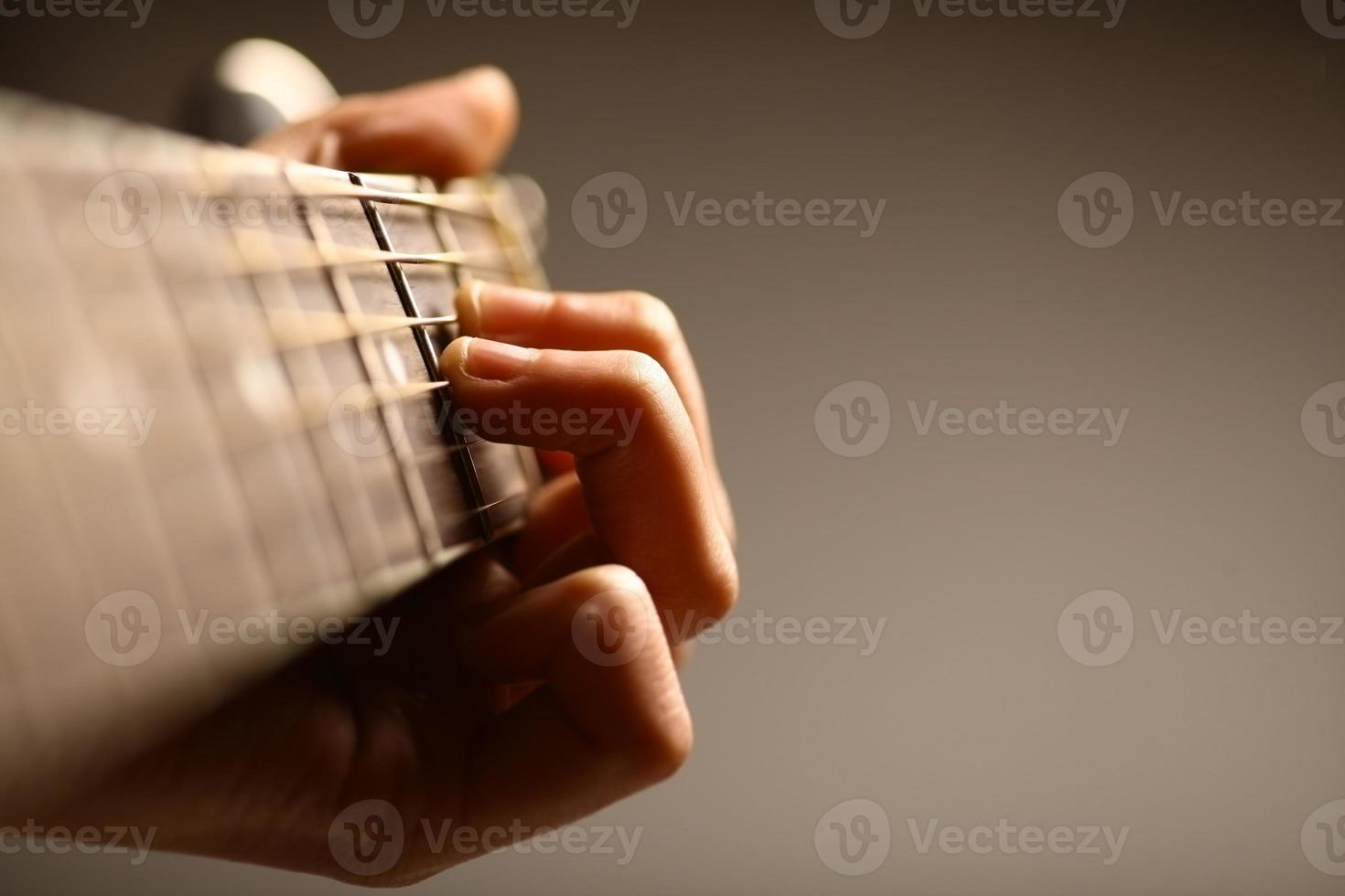 Close-up view of a six string acoustic guitar being held photo