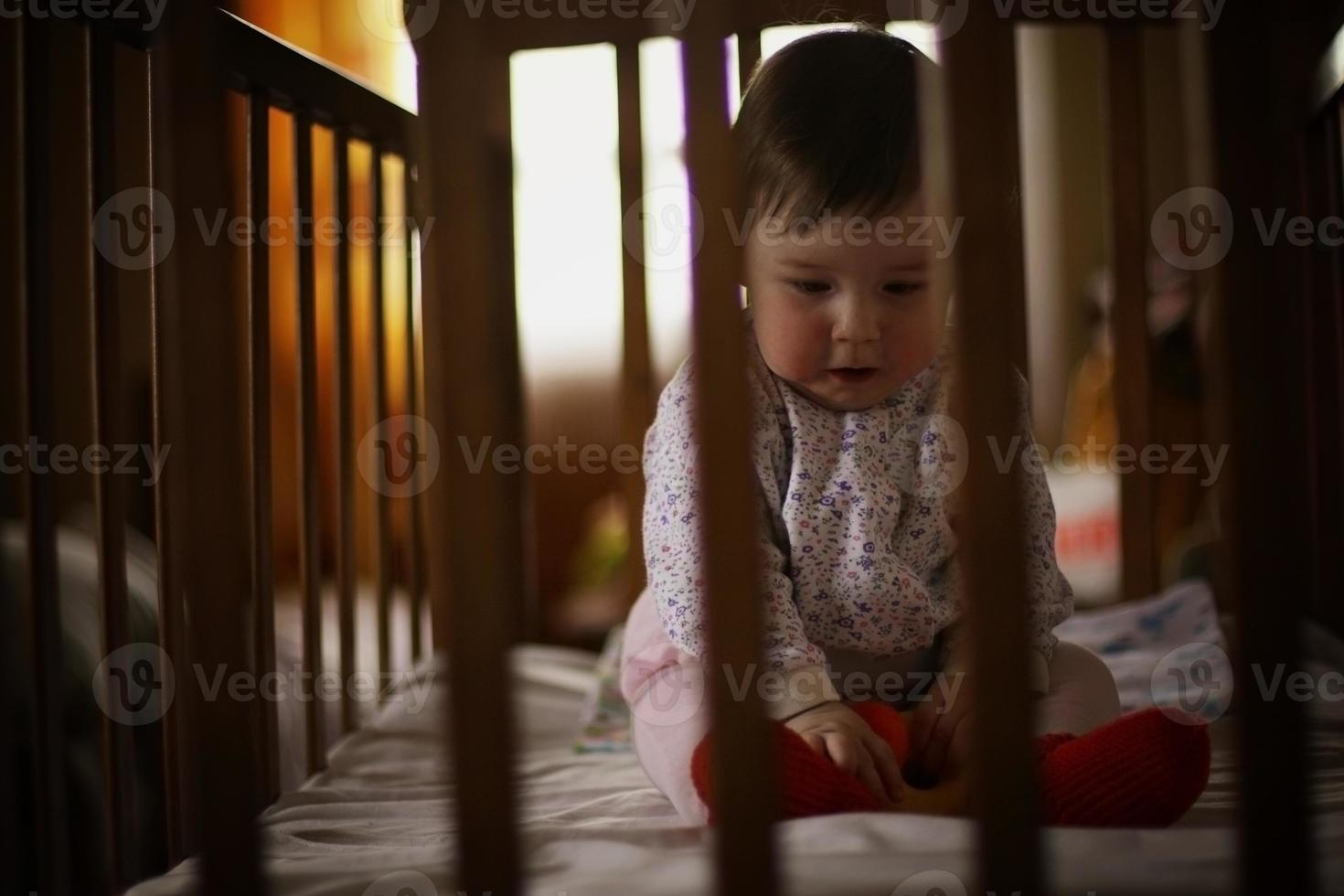 child playing in the bed behind bars photo