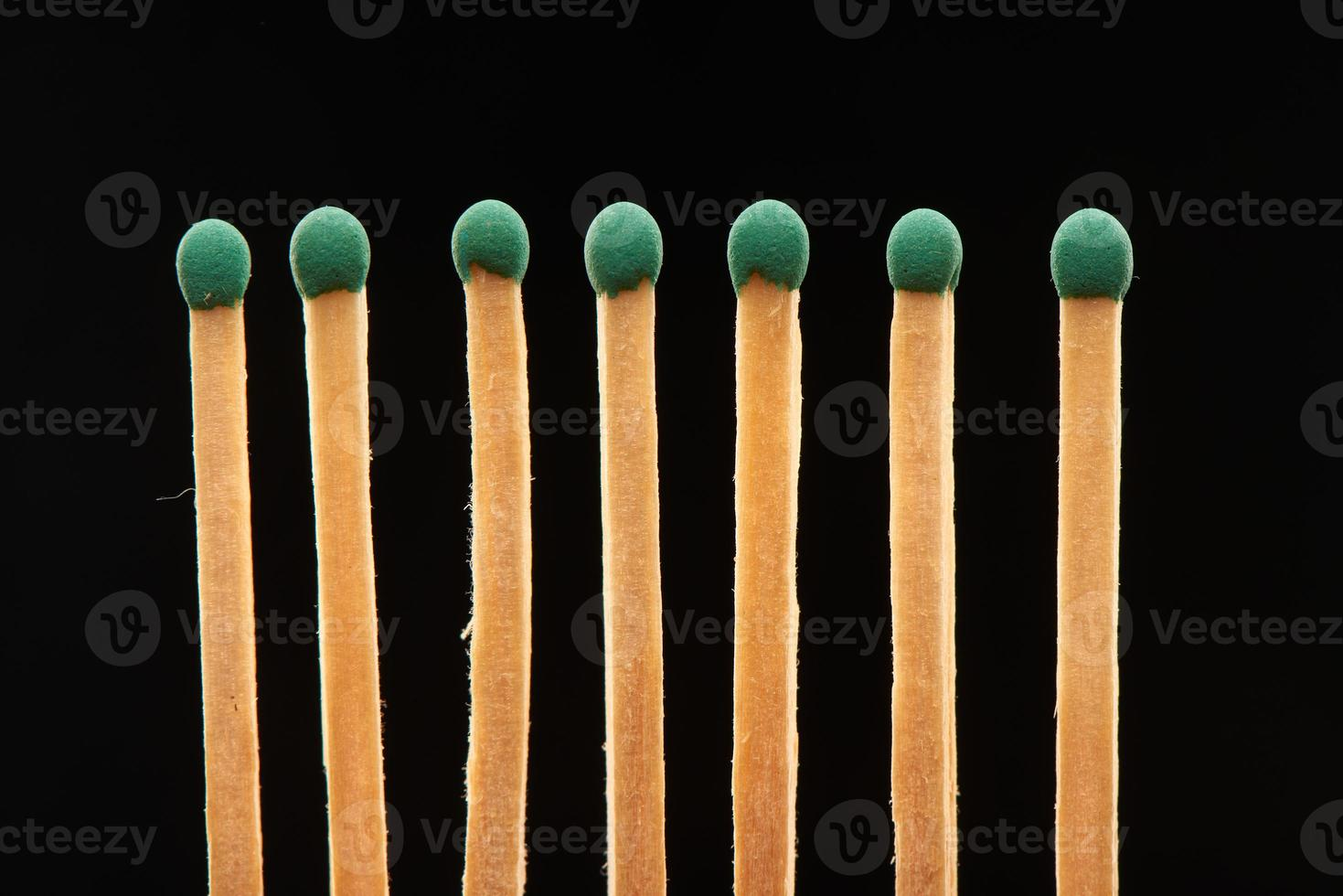 Set of seven green wooden matches isolated on black background photo