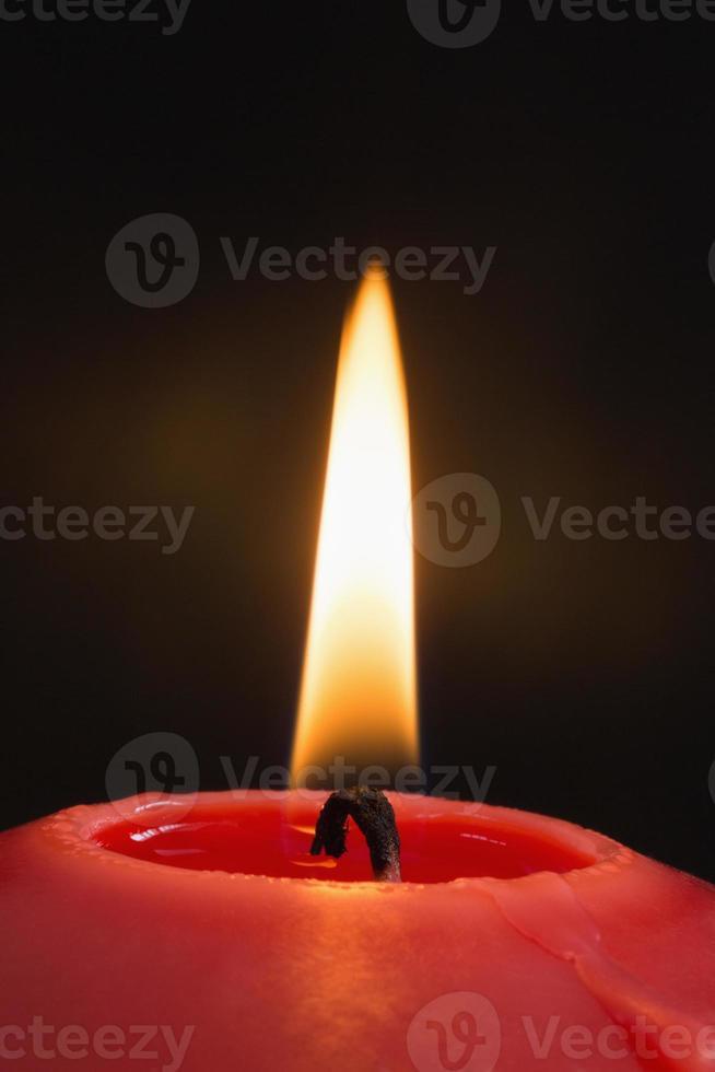 Cerca de una vela roja encendida foto