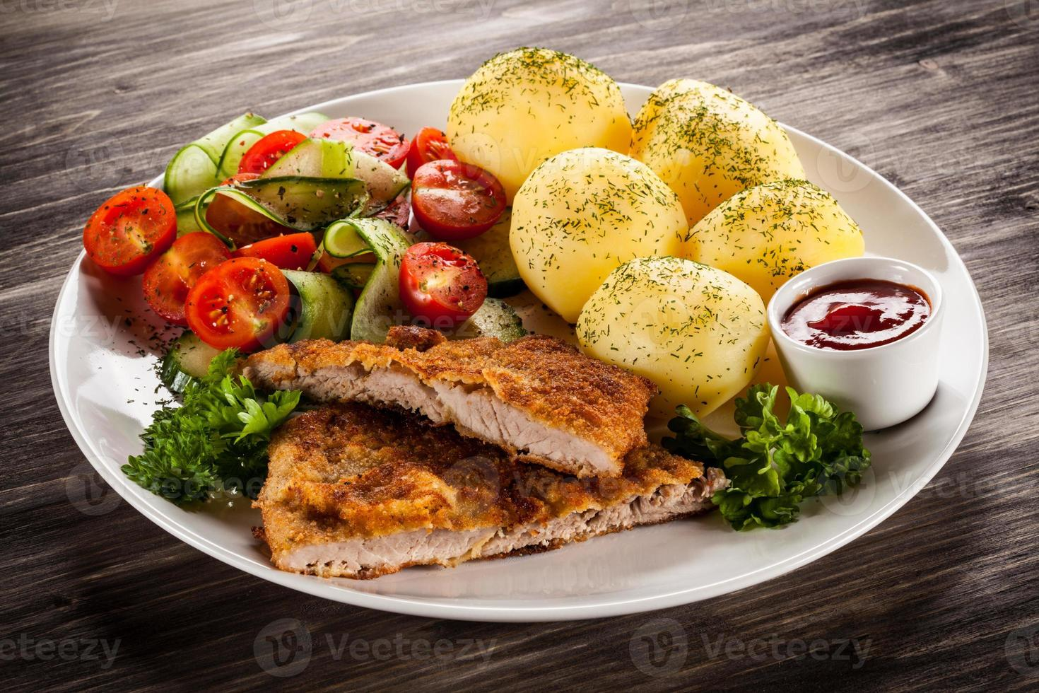 Fried pork chops, boiled potatoes and vegetables on wooden background photo