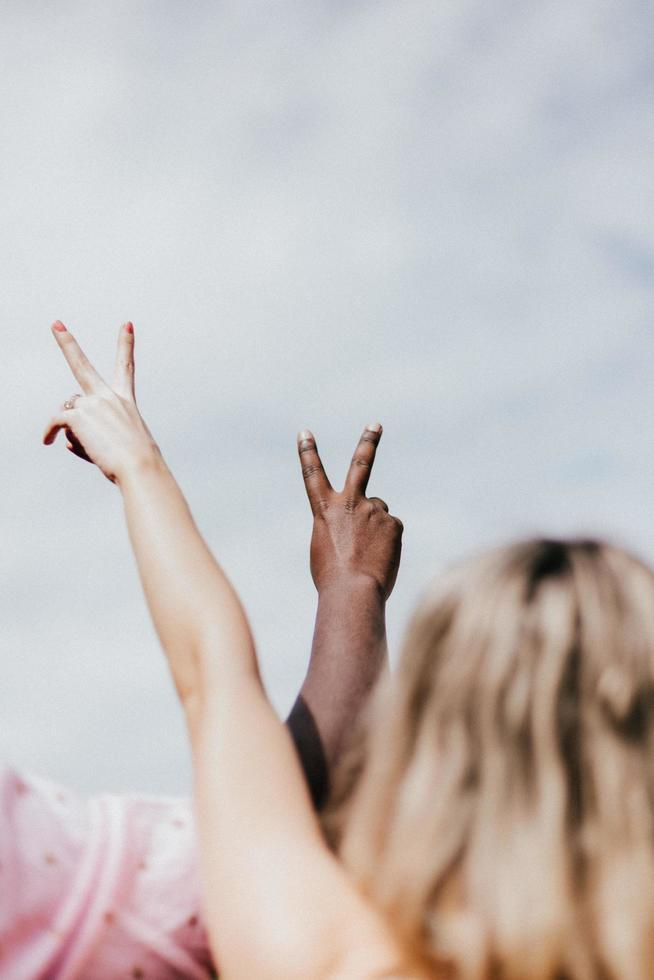 Two people giving the peace sign in the air photo