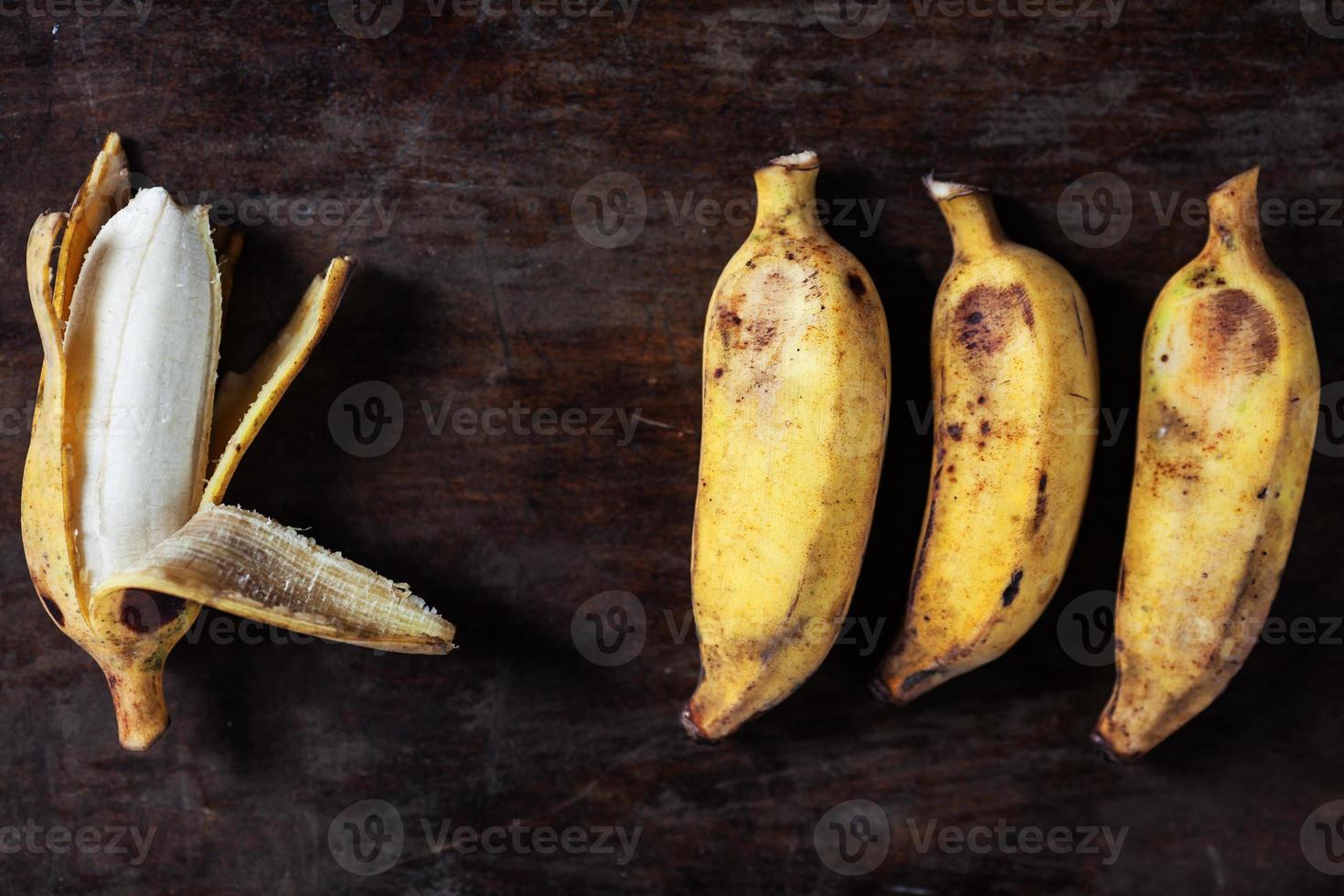 Four bananas on a dark table photo