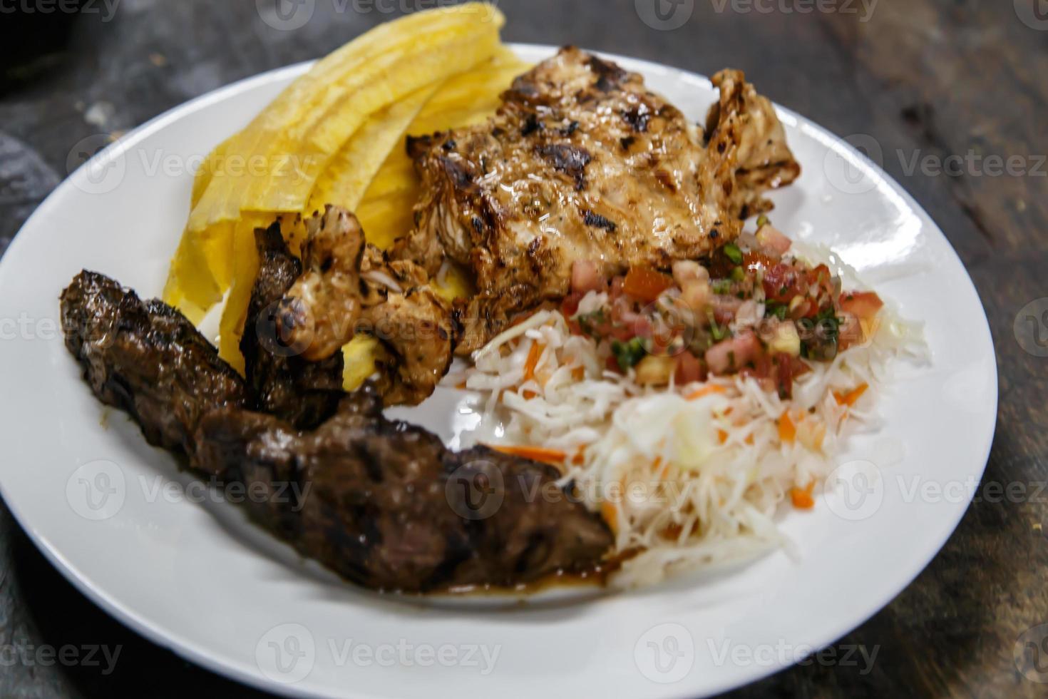 traditional nicaraguan cuisine, roast meat, salad and fried banana. photo