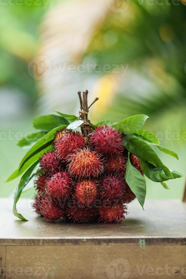 Rambutan fruits and leaves in a bunch on the table photo