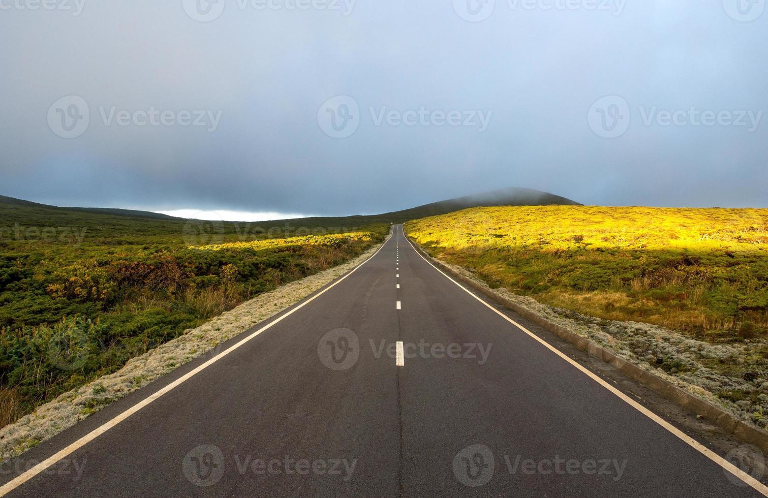 estrada entre colinas com nuvens e sol (açores) foto