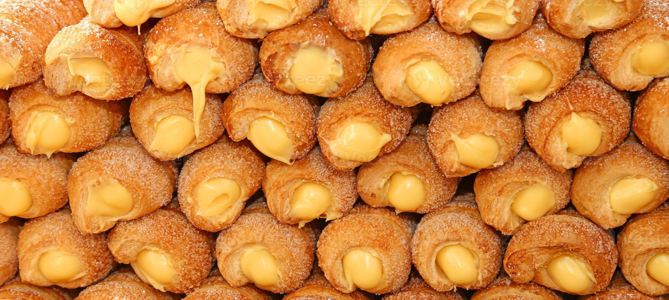 muchos pasteles y crema cannoli a la venta en pastelería foto