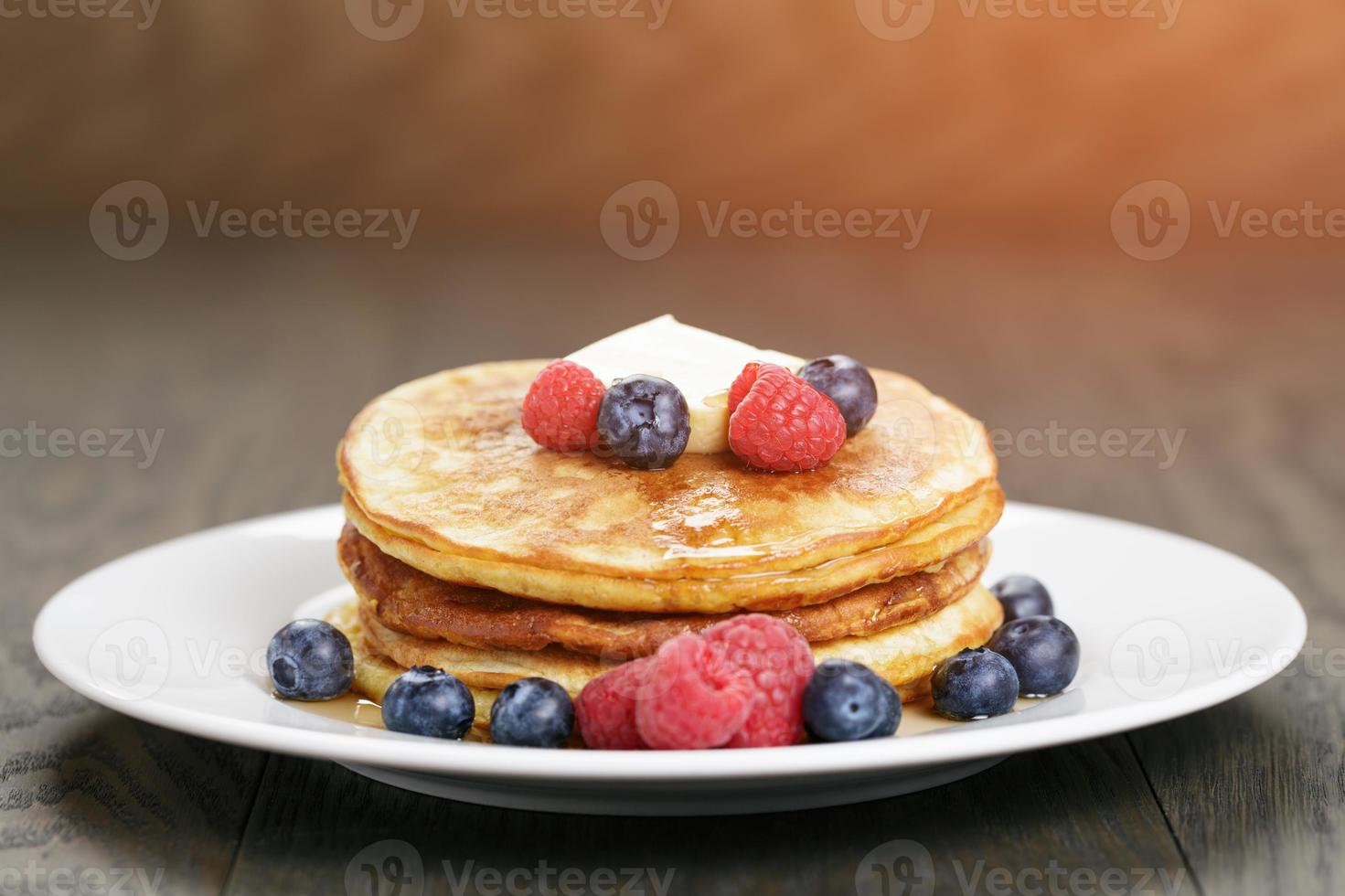 Classic pancakes with butter berrys and maple syrup photo