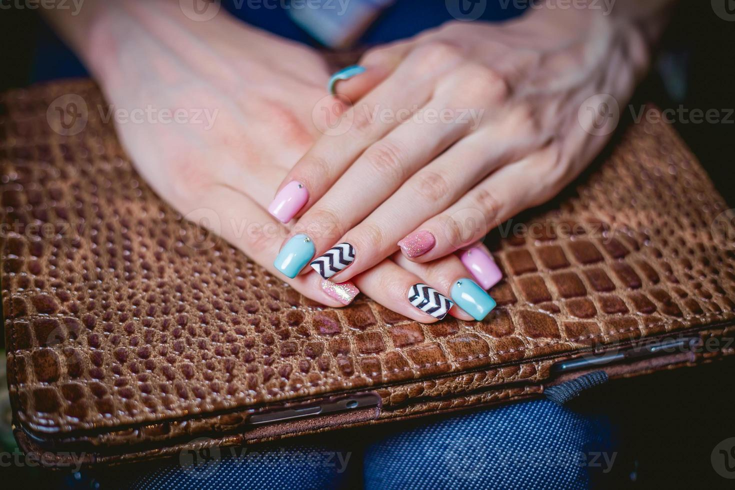 Women's manicure on a background of crocodile skins photo