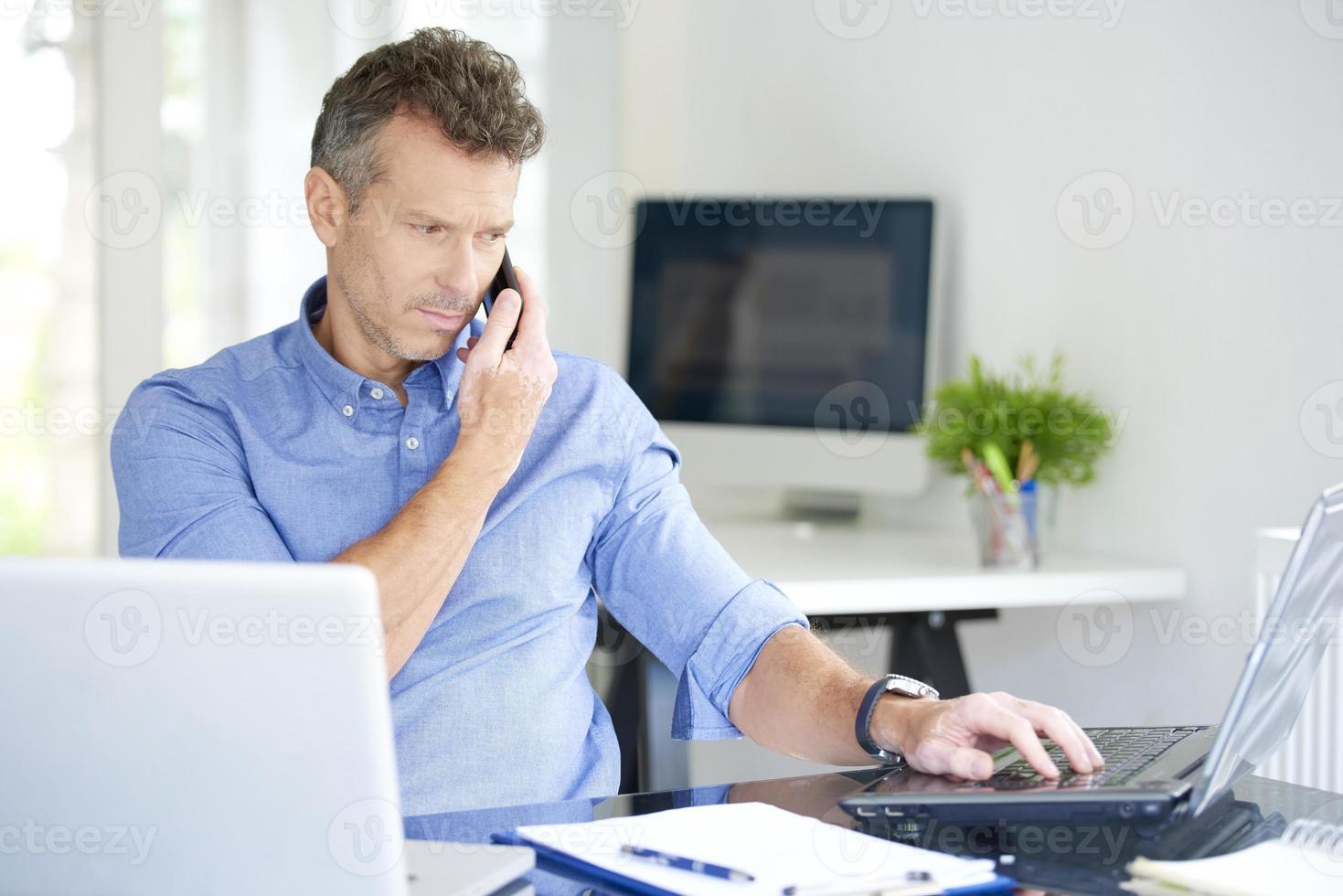 empresario con teléfono móvil y portátil en la oficina foto