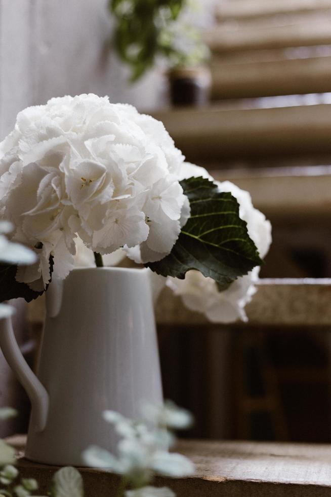 flores blancas en un jarrón sobre escalones de madera foto