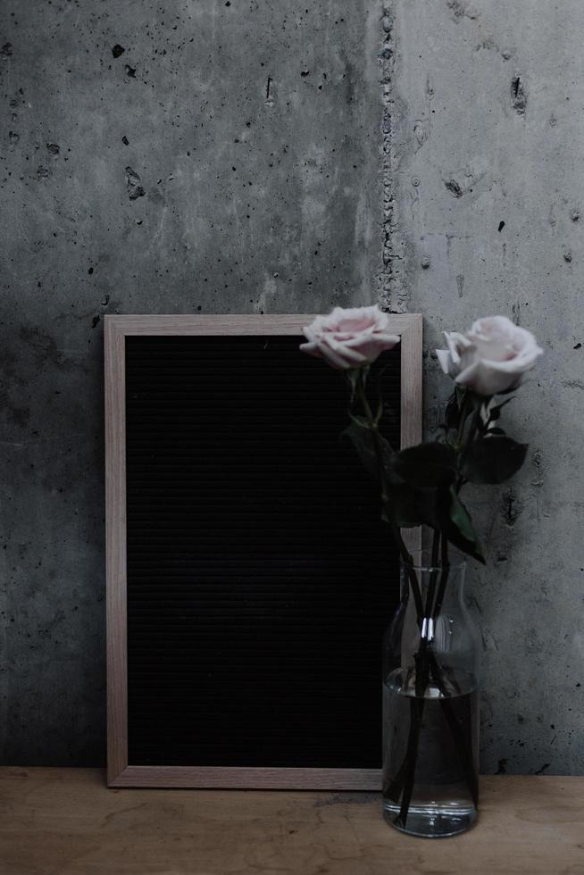 Rosas en un jarrón junto al tablero en blanco en la pared neutra foto